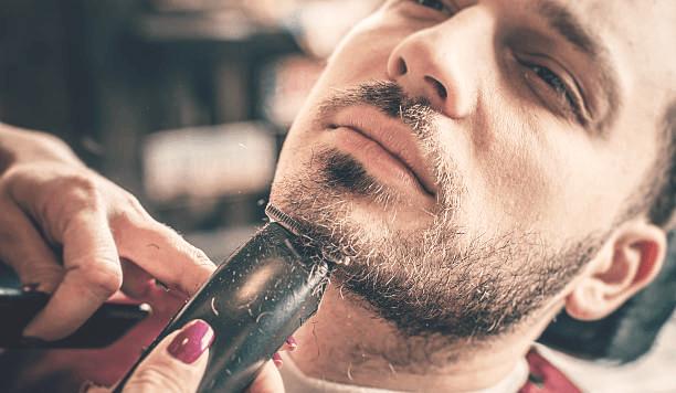 Триммер бреет человека